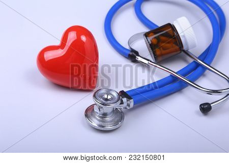Stethoscope, Red Heart And Assorted Pills On White Table With Space For Text