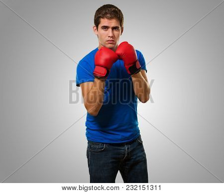 Young Man Wearing Boxing Gloves against a grey background