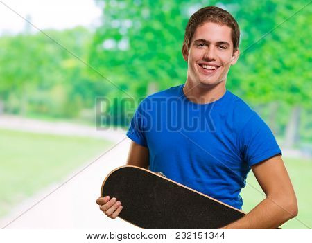 Happy Man Holding Skateboard at a park