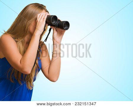 Pretty Woman Looking Through Binocular against a blue background