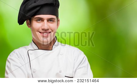 Portrait Of A Young Chef With Hands Folded against a nature background