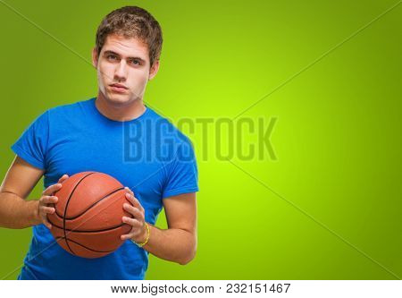 Handsome young man holding a basketball against a green background
