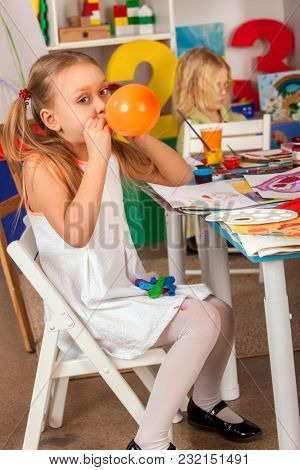 Break school in painting class. Small student painting in art school class. Physical education of little girl playing with balloon. Girl puffs up orange balloon.
