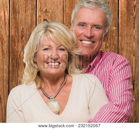 Portrait Of Happy Mature Couple against a wooden background