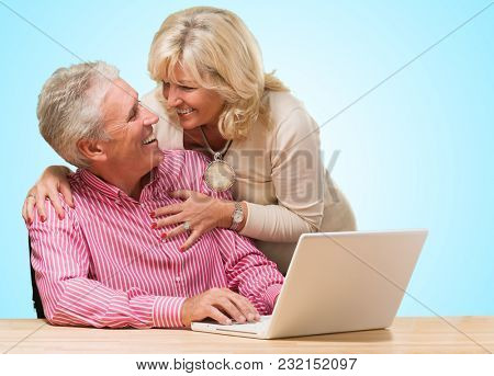 Portrait Of Happy Couple Looking At Each Other against a blue background