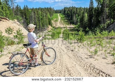 Traveller Boy With A Bicycle Stands On A Road Descending From The Mountain In The Summer In The Fore
