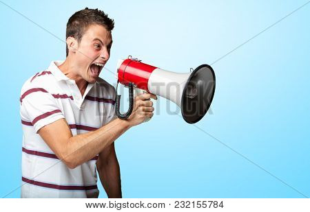 Young Man Shouting In Megaphone On Coloured Background