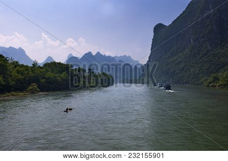 Yangshuo, China - August 1, 2010: A Traditional Raft And Boats With Tourists Cruising In The Li Rive