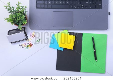 Close-up Of Comfortable Working Place In Office With Laptop, Notebook, Glasses, Pen And Other Equipm