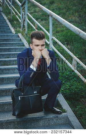 Sad Young Attractive Business Man Dressed In A Blue Suit With A Red Tie Holding A Briefcase Sitting