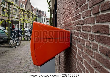 Orange Netherlands Mailbox Post, Mounted On A Brick Wall