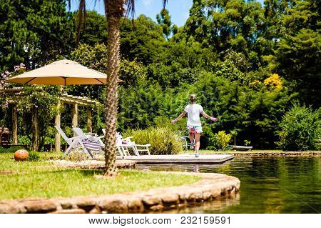 Attractive Young Woman Jumping Rope In Tranquil Location, Peaceful Lake With Garden. Cunha, Sao Paul