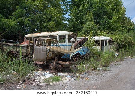 Old Rusty Trucks And Buses At Abandoned Industrial Area.