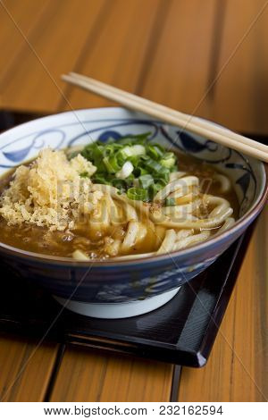 Close-up Of A Bowl Of Curry Beef Udon With Chives And Tempura Crumbles.