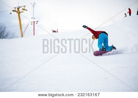 Picture of athlete with snowboard jumping on snowy hill