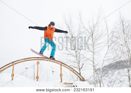Image of young sportive man skiing on snowboard with springboard against background of trees