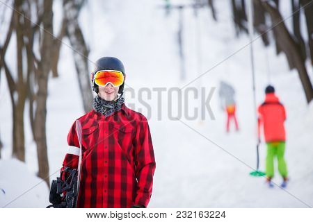 Photo of sporty man with snowboard against background of winter park with trees and people
