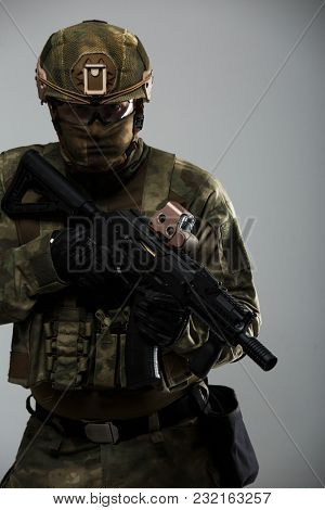 Image of military man in camouflage with gun