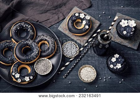 Black and white sweets and charcoal lemonade on a dark wooden background