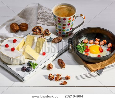 Round Camembert Cheese, Pieces Of Smoked Sausage And A Round Black Cast-iron Frying Pan With A Fried