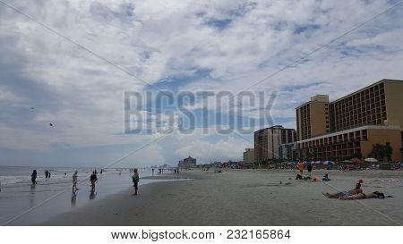 Looking Down The Coast Along The Shoreline With The Ocean And Surf On One Side And A Row Of Hotels O