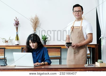 Young Asian Man Barista Serving A Coffee Cup In Cafe Background, Small Business Owner, Food And Drin