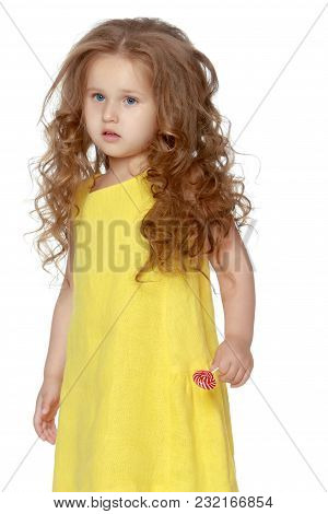 A Little Girl Licks A Candy On A Stick. Isolated On White Background.
