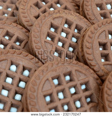 Detailed Picture Of Dark Brown Round Sandwich Cookies With Coconut Filling Close Up. Background Imag