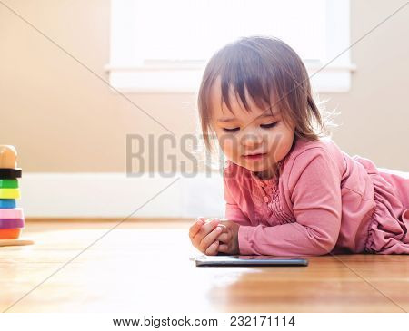 Happy Toddler Girl Playing With Her Tablet Computer In Her House