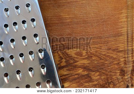 The Chrome Grater Lies On The Cutting Board With A Lot Of Scars From The Ax And Knife. Background Im