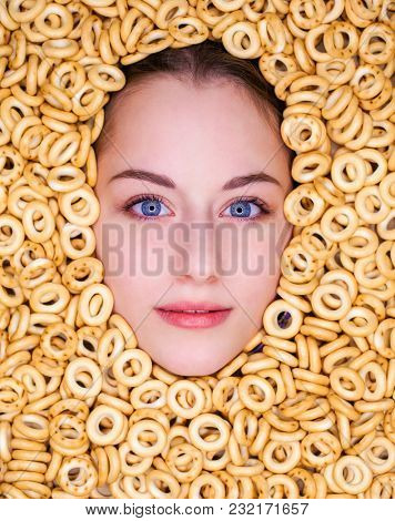 Young beautiful woman face in little fresh bagels