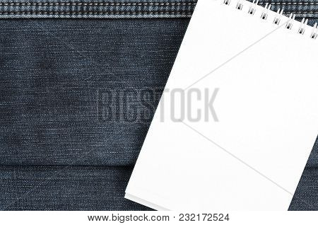 White Notebook With Clean Pages Lying On Dark Blue Jeans Background. Image With Copy Space