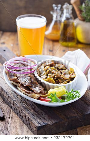 Gyro Plate With Rotisserie Meat On A Pita And Vegetables With A Glass Of Beer
