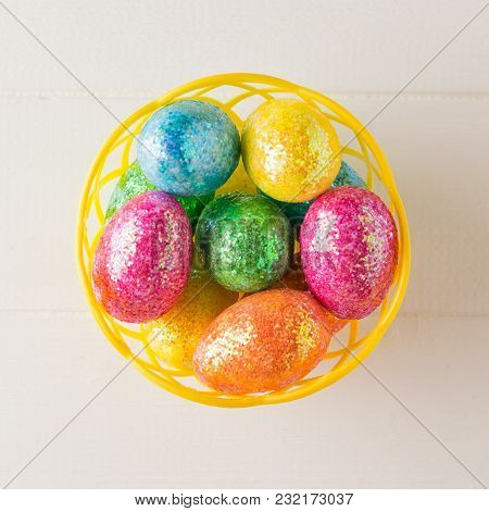 Basket With Colorful Eggs On A White Rustic Table. Decorations For The Easter Table. The View From T