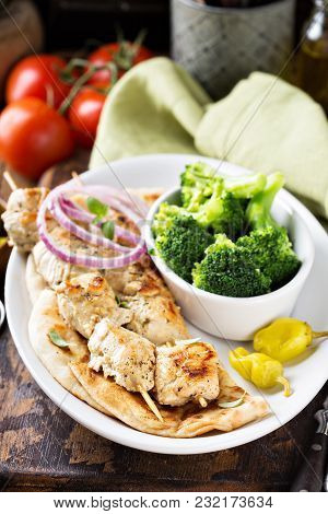 Grilled Chicken Kebabs On A Pita With A Side Of Stemed Broccoli