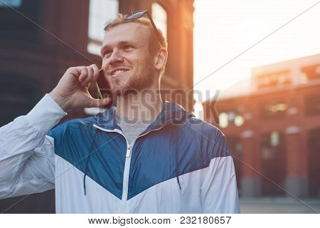 Smiling Man Speaking On The Mobile Phone On The Street, Outdoors
