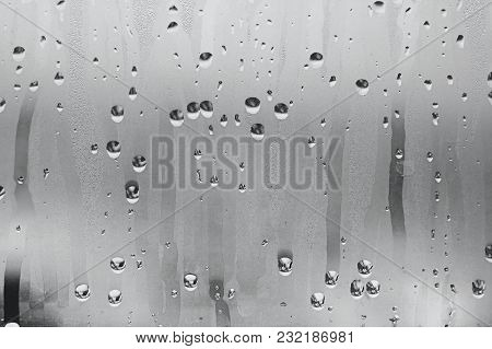 Black And White Background Of The Condensate Flowing Water On The Window Glass. Collecting And Strea