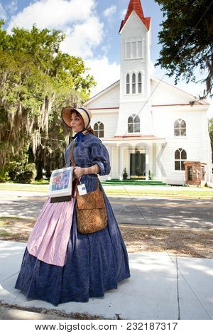 BEAUFORT, SOUTH CAROLINA, USA-JUNE 25, 2013: A tour guide dressed in period clothing gives a tour of old Beaufort, South Carolina in front of the historic Tabernacle Baptist Church.