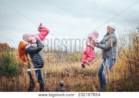 Happy Family With Two 1 Year Old Girls Have Rest In A Field Full Of Yellow Grass