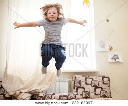 child jumping on the bed in the bedroom.