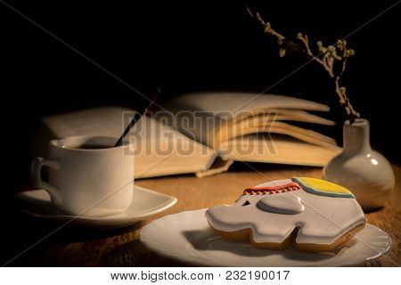 An Open Book And A Cup Of Coffee On The Table. Vase With A Branch Of Apricots And A Book On The Tabl