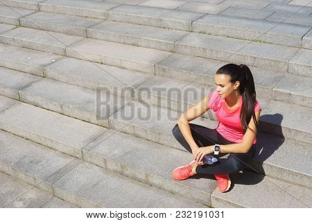 Young, fit and sporty girl resting after the training.