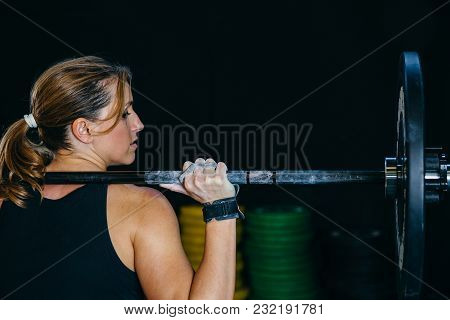 Back View Of A Young Sporty Woman Doing Back Push Press Or Military Press Exercise With A Barbell Ov