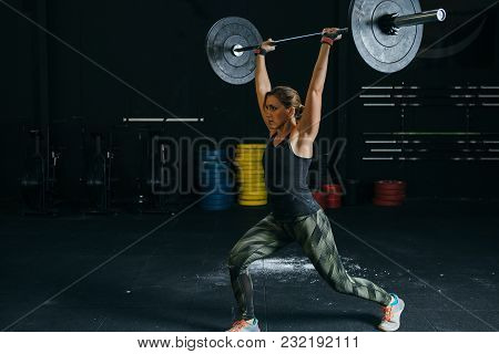Young Woman Athlete Does Jerks With Barbell At Box Gym On A Fitness Routine. Copy Space Area Availab