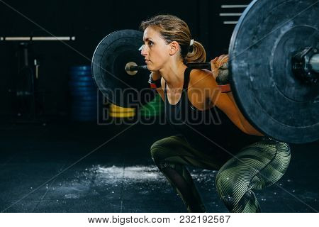 Young Athlete Woman Does Back Squat Exercise On A Fitness Routine At The Box Gym