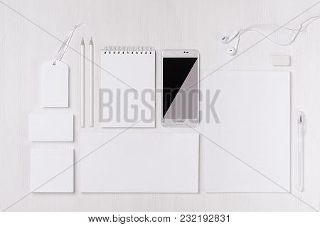White Blank Stationery As Work Place With Phone, Earphone On Light White Wood Background. Branding M