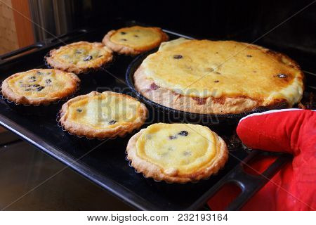 Extraction Of Ready-made, Hot Cheesecakes From The Stove