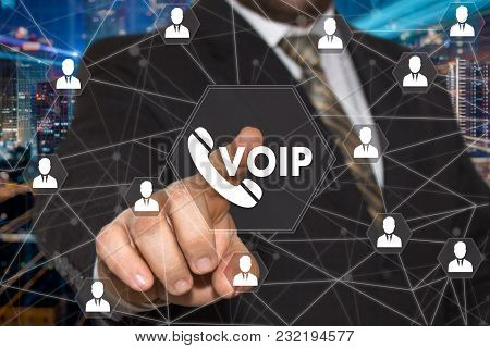 The Businessman Chooses Voip Button On The Touch Screen With A Futuristic Background .the Concept  V