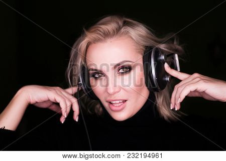 Fashion Portrait Of A Woman In Headphones Over Black Bsckground.