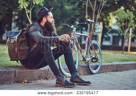 Handsome Hipster Traveler With A Stylish Beard And Tattoo On His Arms Dressed In Casual Clothes And